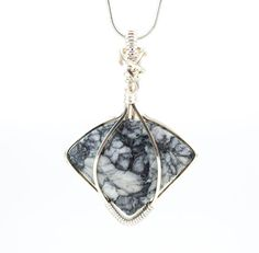 Unique and elegant shape and a beautiful grey and black pattern combine beautifully in this Pinolith pendant necklace. Pendant has been hand wrapped in non tarnish silver plated copper wire and comes ready to wear with an 18 silver plated snake chain with lobster claw clasp. Neutral