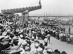 Rudi Weissenstein (on top of the scaffold) taking pictures of the opening of Tel Aviv's new harbour, 1936.  Photo House Pri-Or.