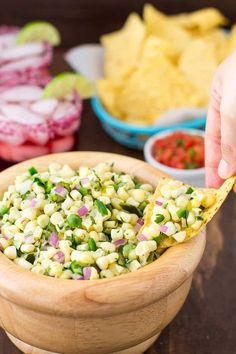 A photo of Chipotle Corn Salsa Copycat in a whod bowl. The yellow corn and red onion are served on a tortilla chip held by a hand to the right of the photo. There is a blue basket with tortilla chips and a margarita in a pink clear glass in the background.
