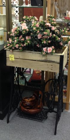 Sewing machine base repurposed into a planter with pallet wood