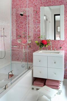 Contemporary bathroom features a pink grid tiled wall lined with a frameless medicine cabinet over a white lacquer floating washstand adorned with square knobs topped with white quartz hovering over a plank shelf filled with pink towels.