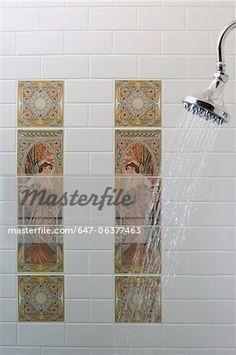 TUILE détail : dans la cabine de douche, carreaux de métro blanche, carreaux art Art Nouveau de deux femmes, stylisé en médaillon rectangulaire de tuile d'art, pomme de douche nickel poli