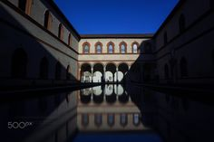 Between the shadows... - This is an atrium in the museum, inside Castello Sforzesco, in Milano - Italy.  On a sunny winter day, people just enjoy the warm light.  The long exposure gives a fine touch to the reflection...