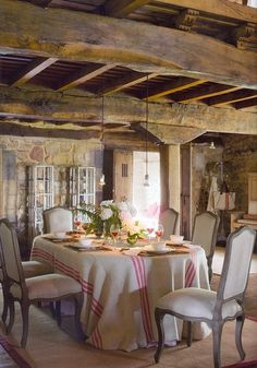 charming French styled dining room - chairs, linen table cloth, carpet, wooden beams, stone walls
