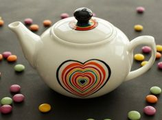 "Small Teapot from the Scrabble collection. Rainbow heart on one side and message on the other: ""I love thee more than tea"" Hand Painted Ceramics by artist Caro Spinette. Photo by Kate Sims"