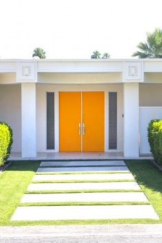Clean white architecture. Bold color double doors with sidelights. Flush concrete pavers .