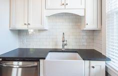 Grey and white - clean and modern kitchen. White subway tile, farm sink, stainless steel appliances, black quartz countertop» Sara Eastman Photography, LLC