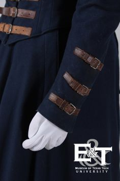 1870s Two-Piece Navy, Wool Riding Habit. Museum of Texas Tech University has a fitted bodice, pointed in the center front and has a bodice opening which fastens with brown leather, buckled straps in the front.  The high-standing collar, sleeve cuffs and squared tails in the back are also trimmed and fastened with the buckled leather straps.  The long-trained skirt has two gores; an unusual cut with an inset that cups to allow space for fitting over the saddle.