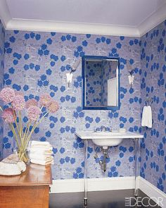 DESIGNER BATHROOM VANITIES: KATIE RIDDER'S VINTAGE BATHROOM    Finnish wallpaper from the 1950s adorns the walls of the powder room in a Manhattan apartment decorated by Katie Ridder. Hanging above a simple yet stylish Waterworks sink, a vintage FontanaArte mirror echoes the wall color.