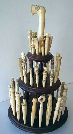 A collection of 46 antique carved whalebone and whale ivory bodkins on a custom made display stand.