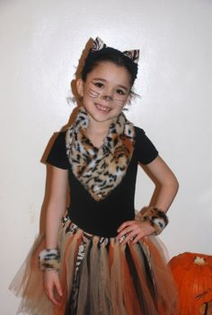 Tiger Themed Tutu Costume by CraftyGuides.com Purchase about 1/2 yard Tiger Print fabric or Ribbon and bring around child's neck and pin. Tie tiger print ribbon strips in between every couple of tulle strips of a basic tutu comprised of orange, gold and black tulle.