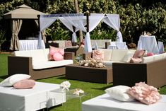 The lounge area will have a rattan sofa set with matching rattan coffee table and two white lounge ottomans spread out around the lawn games with pillows in shades of yellow, green, and blush.