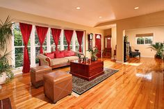 Such a gorgeous combination with the red curtains, red door, gorgeous hardwoods and leather furniture
