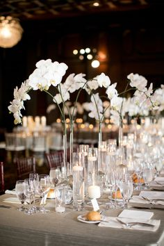 White Phalaenopsis orchids can add tons of style to your reception. Here, Jackson Durham Events created delicate arches over these tables by arranging two of the multi-flower stems in glass vases with tall, narrow necks. Coral Wedding Centerpieces, Lantern Centerpiece Wedding, Orchid Centerpieces, White Wedding Bouquets, Wedding Flower Arrangements, Wedding Flowers, Wedding Decorations, Lantern Wedding, White Orchid Centerpiece