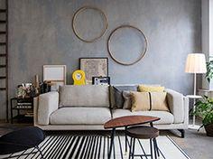 Moderne woonkamer met comfortabele grijze bank en accessoires in Scandinavische…