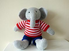 Little grey boy elephant wearing a red and white striped jumper and blue shorts.  Body and clothes are both made from luxury cotton yarn. Jumper closes at the back with a small button. Elephant has been stuffed with polyester stuffing.  This cute elephant would make a delightful