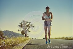 Beautiful fit woman in sport shorts running on a road at sunrise or sunset. Healthy lifestyle concept.