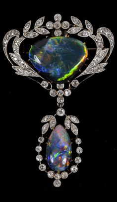 A BELLE EPOQUE BLACK OPAL AND DIAMOND BROOCH. The central section of black opal is set within a foliate surround of circular-cut diamonds and suspends a pear-shaped black opal in a similar surround, in silver and gold, 5.5 x 3.5cm.