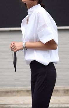 white short sleeve top, silver watch, minimal clutch & black pants