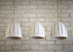 These pendant lights are hand made of white stoneware. They may be hung above your dining room table or in any other room.  You can choose to have as many pendants as you would like and create your own chandelier. For any number of lamp shades other than three, please contact me for pricing.  Lamp shade specification *Shade measures 7.5 (19 cm) in height and 6.5 (16 cm) bottom opening. * Each shade takes one E27 light bulb. * The length of cord is according to request. * The shades come with…
