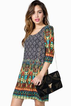A short shift dress featuring an ethnic-inspired border print and a scoop neck. Three-quarter sleeves. Exposed back zip closure. Finished hem. Fully lined. BOUTIQUE FIVE.