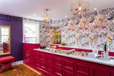 A purple wall is countered with a hot pink bar with a white countertop stretching the length of the room. A black and white rose floral wall is decorated with bright multicolor butterflies. Butterflies hanging in the wire case surrounding the light bulbs bring the creatures to life with a 3D look. A food display is perfectly organized down the long countertop.