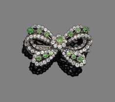 A demantoid garnet and diamond bow brooch The openwork bow set throughout with…