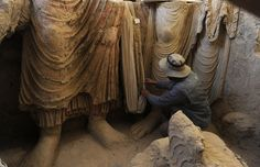 An Afghan archaeologist examined Buddha statues inside an ancient monastery at Mes Aynak, in eastern Logar Province, in 2010.