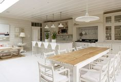 Natural dining table. Love the pots hanging in the kitchen