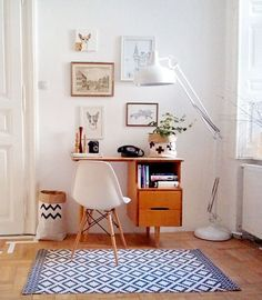 Mid Century Modern workspace with white walls, blue geometric rug, and white Eames chair.