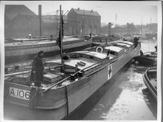 WWI; A tug towing a hospital barge down a canal in north west France. | First World War Poetry Digital Archive