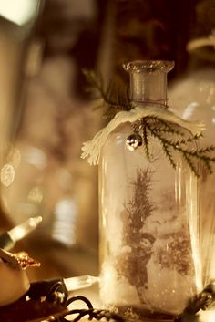 A sweet photo placed in a vintage glass bottle with a sprig of greenery and a little bell.