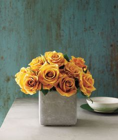 Cluster Of Yellow Roses Centerpiece: For stiff-stemmed flowers, like roses, irises, and mums, a low cube guarantees a graceful grouping. Cement Cube Vase, JamaliGarden.com.