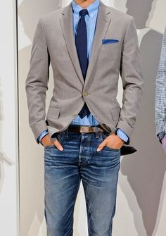 Shop this look on Lookastic: https://lookastic.com/men/looks/blazer-dress-shirt-jeans-tie-pocket-square-belt/1747 — Grey Blazer — Blue Dress Shirt — Navy Tie — Brown Leather Belt — Blue Jeans — Navy Polka Dot Cotton Pocket Square
