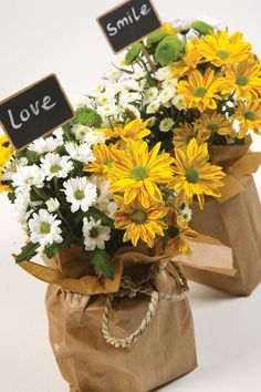 It's Raining Sunshine. Shopping belongs in a shopping bag, but sometimes a mega-message can be conveyed in a small brown paper bag. Use a plastic container and oasis foam as a base. Arrange yellow and green Chrysanthemums at random. Adding sunshine and focus with an attractively marked variety. The label is easily customised by adding the name of the recipient or a kind message.