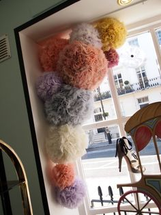 Window display...I could do this with colorful tissue paper pom flowers