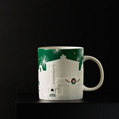 A white ceramic mug featuring Berlin's iconic monuments, decorated for Christmas.