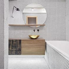 This bathroom is all covered in white penny tile with black grout. The bold move embellished with minimalist black and brass fixtures sleek wood carpentry and statement brass bowl sink.   design by Dagmar Štepánová of Formafatalin Prague /   Fine-line wood: European Walnut   picture via @baars_bloemhoff /  #walnut #woodcraft #interiordesigninspiration #furnituredesign #furnituredecor #italiandesign #italianfurniture #bathroomtrends #mosaic #architecturedesign #designlovers #archdaily…