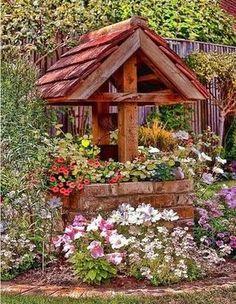 Un pequeño pozo en el jardín rodeado de un gran colorido floral