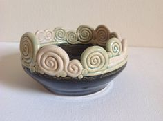 This piece was thrown on the pottery wheel to get a good base, then I added different shaped coils around the upper rim. The bottom half is glazed a shiny black and the upper coils are an iridescent pale green and creamy color. Perfect spot to hold things on your bedside table or would be a wonderful jewelry holder.    Coil pot is 3 inches high and 5 inches across.