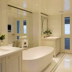 Intarya - bathrooms - master bath, master bathroom, venetian mirror, bathroom with venetian mirror, bathroom venetian mirror, twin washstands, oval bathtub, freestanding oval bathtub, waterfall tub filler, waterfall bathtub filler, floor to ceiling mirror,