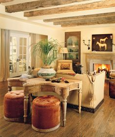 On the ranch...curvy rustic table, great tufted ottomans and the sofa is so perfect.