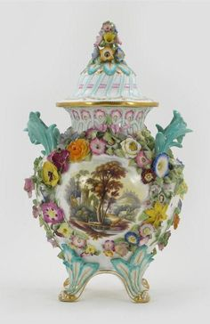 A Coalport flower encrusted vase and cover, one side painted with flowers, the other with a landscape, raised on four feet, pseudo crossed swords mark, c.1840, some restoration to the handles, 36cm. (2)