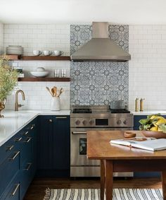Walker Zanger Duquesa Fatima Mezzanotte Tiles accent white subway backsplash tiles and are fixed under a stainless steel vent hood positioned over a stainless steel oven range.