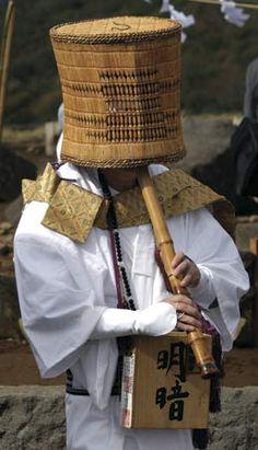 """A Komuso (literally, nothingness monk) of the Fuke Zen sect, wearing a """"tengai"""": a woven straw hat which covers the head completely. The tengai indicates the denial of self, taught by the practice. Komusa also carry and play the """"shakuhachi"""", a bamboo flute."""