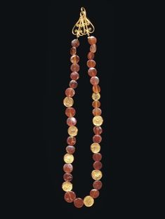 A ROMAN CARNELIAN AND GOLD BEAD NECKLACE   CIRCA 2ND CENTURY A.D.   Composed of thirty carnelian disk-shaped beads interspersed with nine hollow gold sheet disk-shaped beads; strung with a modern openwork palmette hook-and-loop closure  16½ in. (41.9 cm.) long