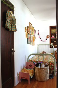 This is awesome for kids bedroom later on. Love the wall stitchery and vintage dress hanging.