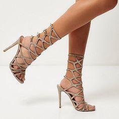 Metallic gold tone Caged design Pin buckle strap fastening Open toe Open heel Slim stiletto heel Heel height 12cm