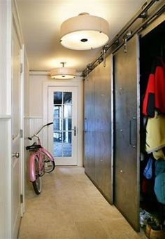 Sliding barn style doors covered in metal. I would love to have a wide hallway that had this much storage on one side, and a bunch of art on the other wall.