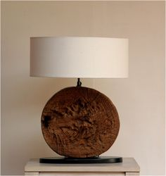 Genta:This circular base of rustic teak shows off the amazing grooves and crevices of inside the wood. Quite a rustic work of art and sits proudly on a metal base. It is great to know that piece of wood is unique so will vary slightly in shape, shadings and size. An individual lamp for your home that no one else will have.